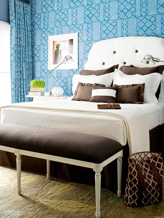 Bedroom with printed blue wallpaper and white and brown bedding