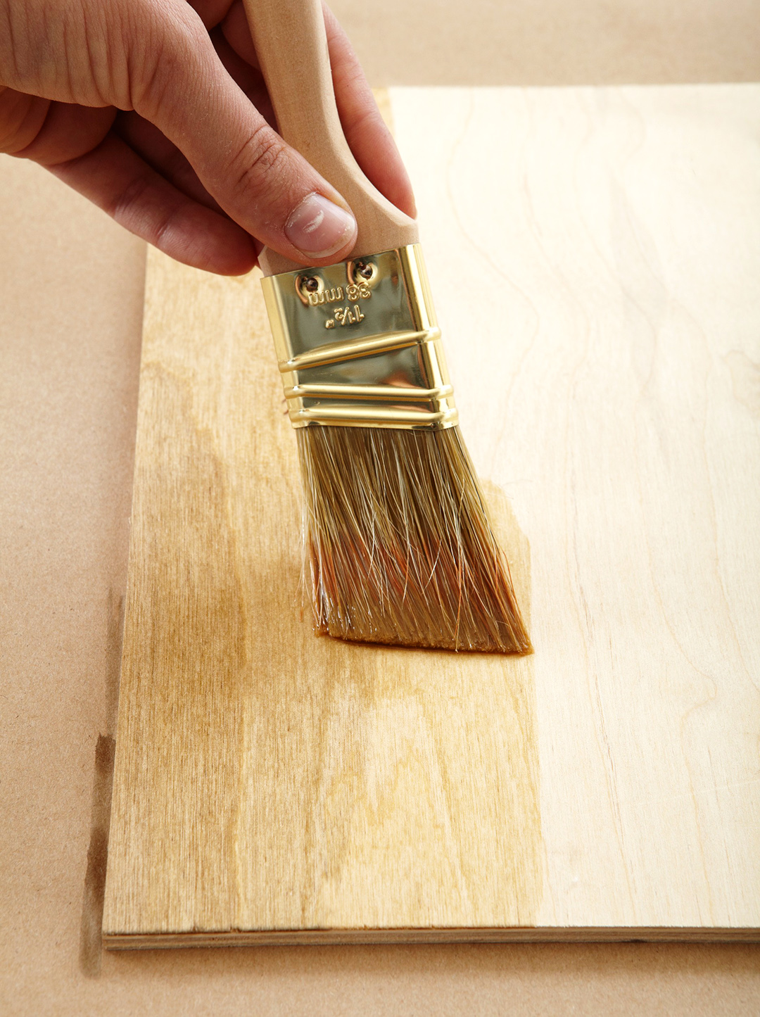 person painting clear stain on piece of wood