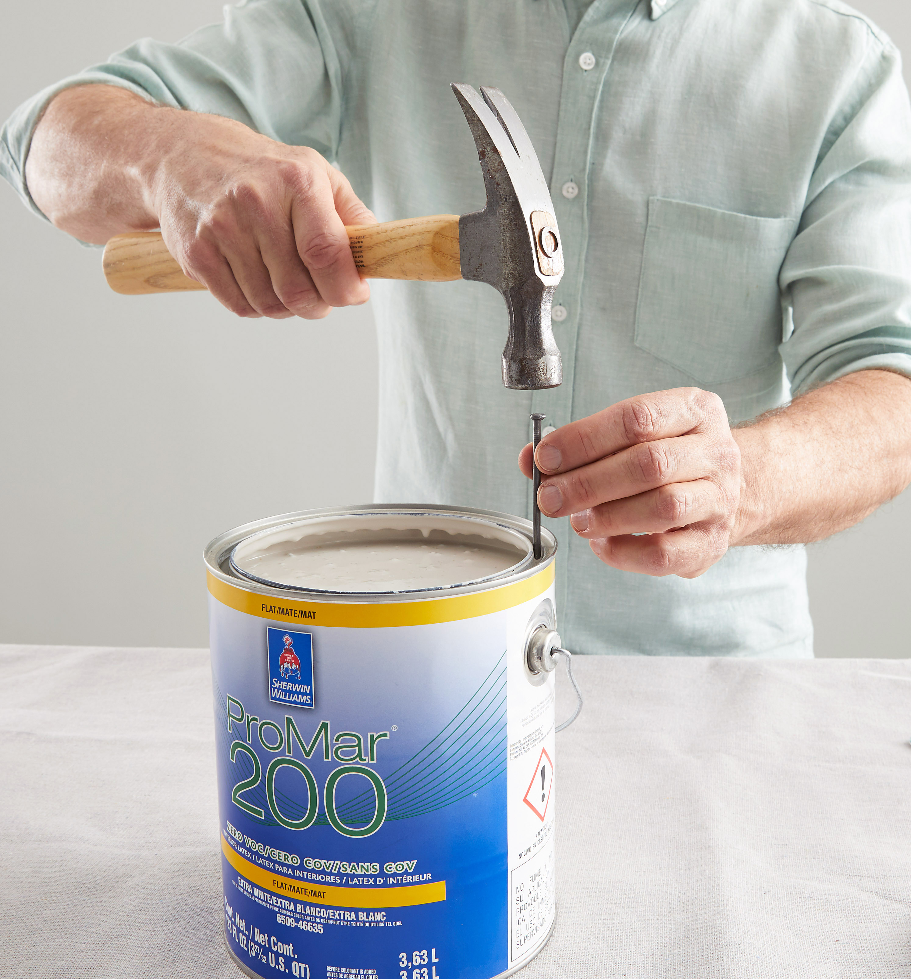 tap nail into paint can top with hammer
