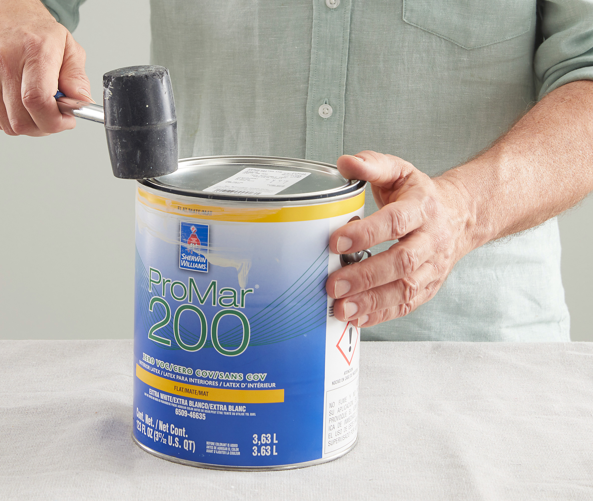 tapping lid with mallet to close paint can