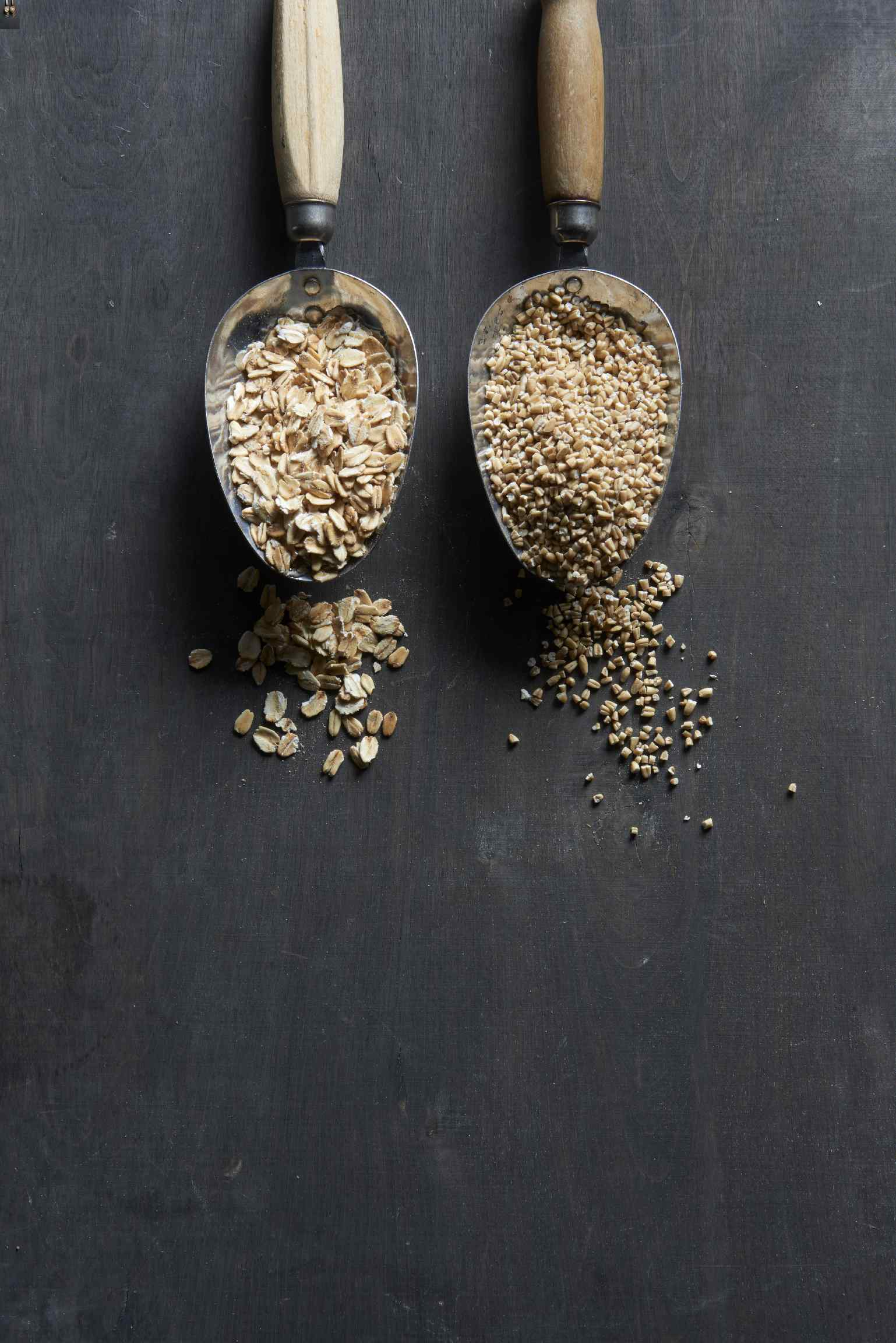 Scoops of rolled oats and steel-cut oats in metal scoops with wooden handles, some oats spilling around the scoop