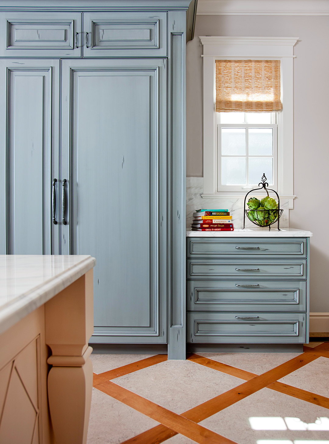 kitchen with blue accent cabinet and drawers by window
