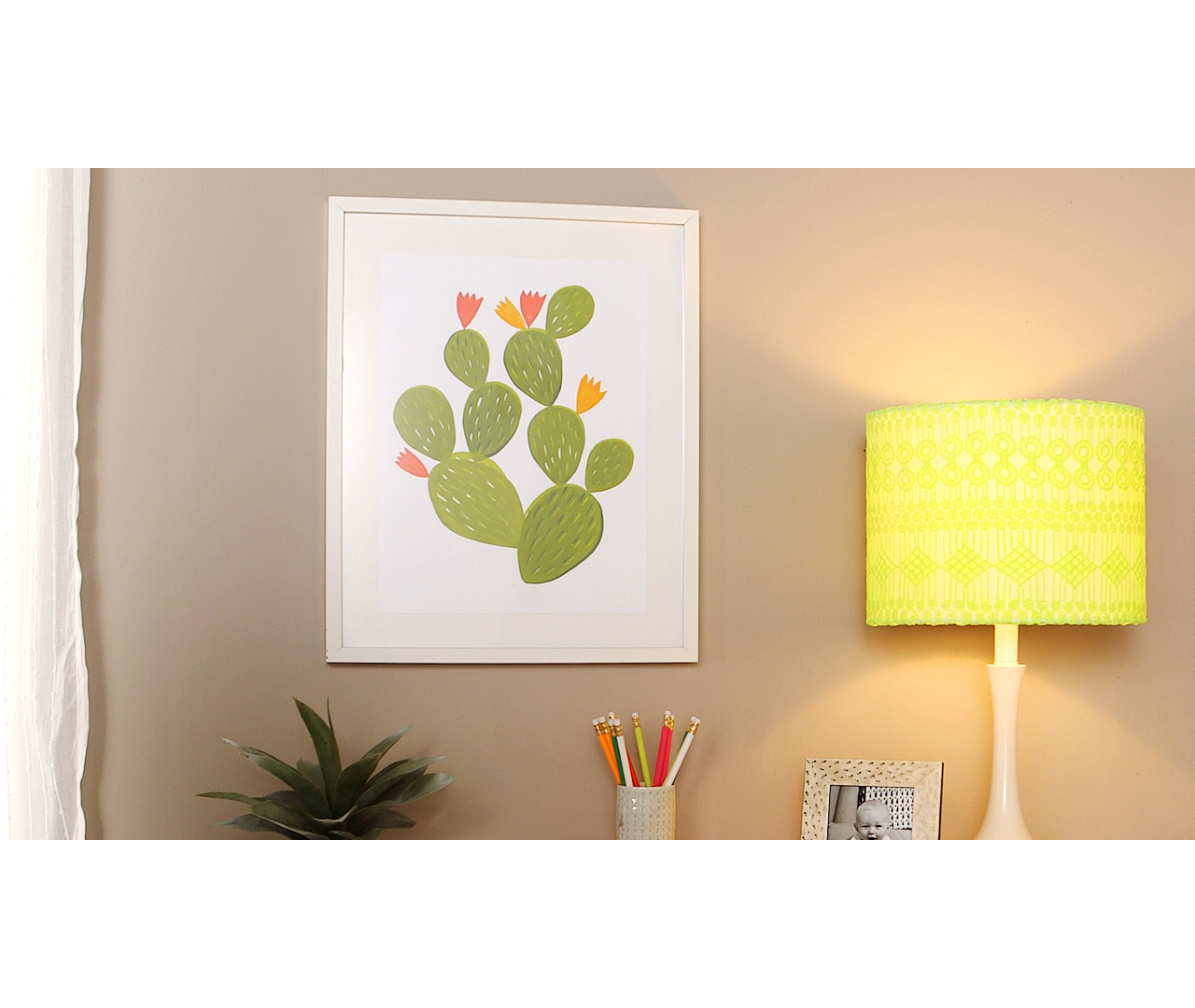 stamped cactus art in white frame on wall
