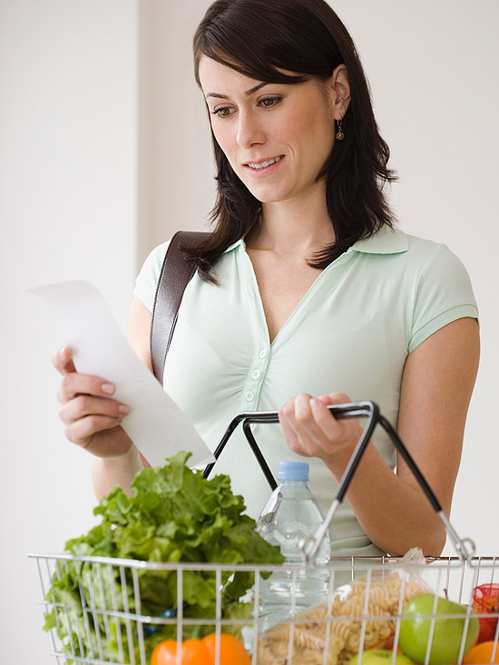 Woman grocery shopping with grocery basked in one hand and grocery list in the other.