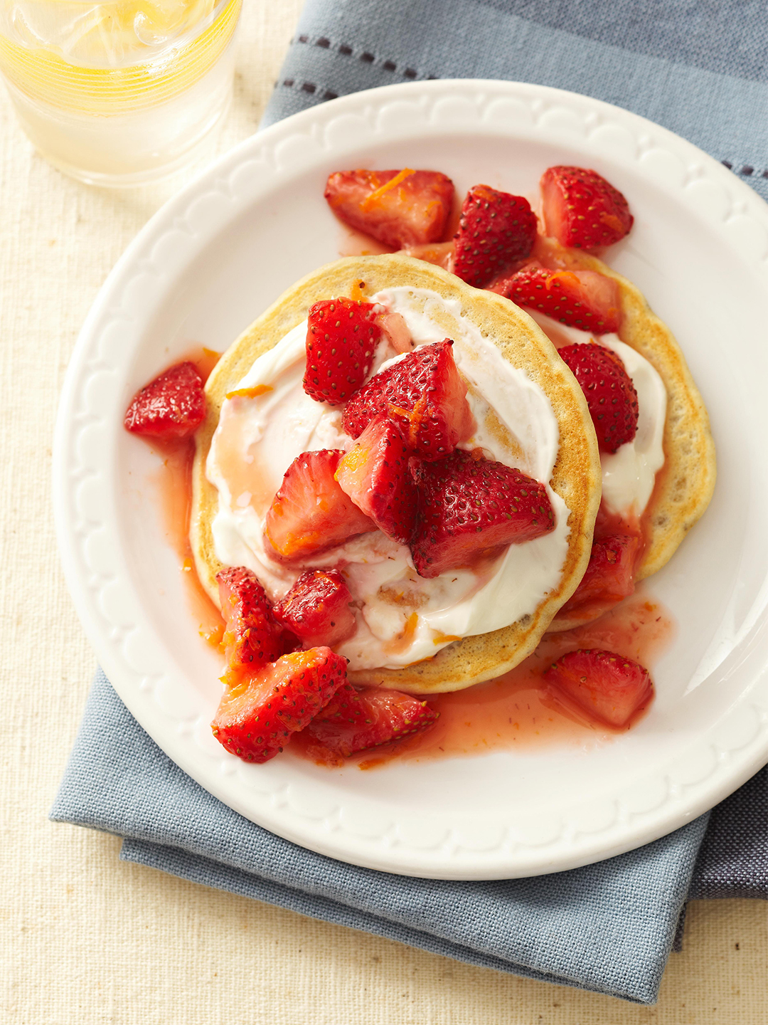 Strawberries and Cream Pancakes on white plate with blue napkin