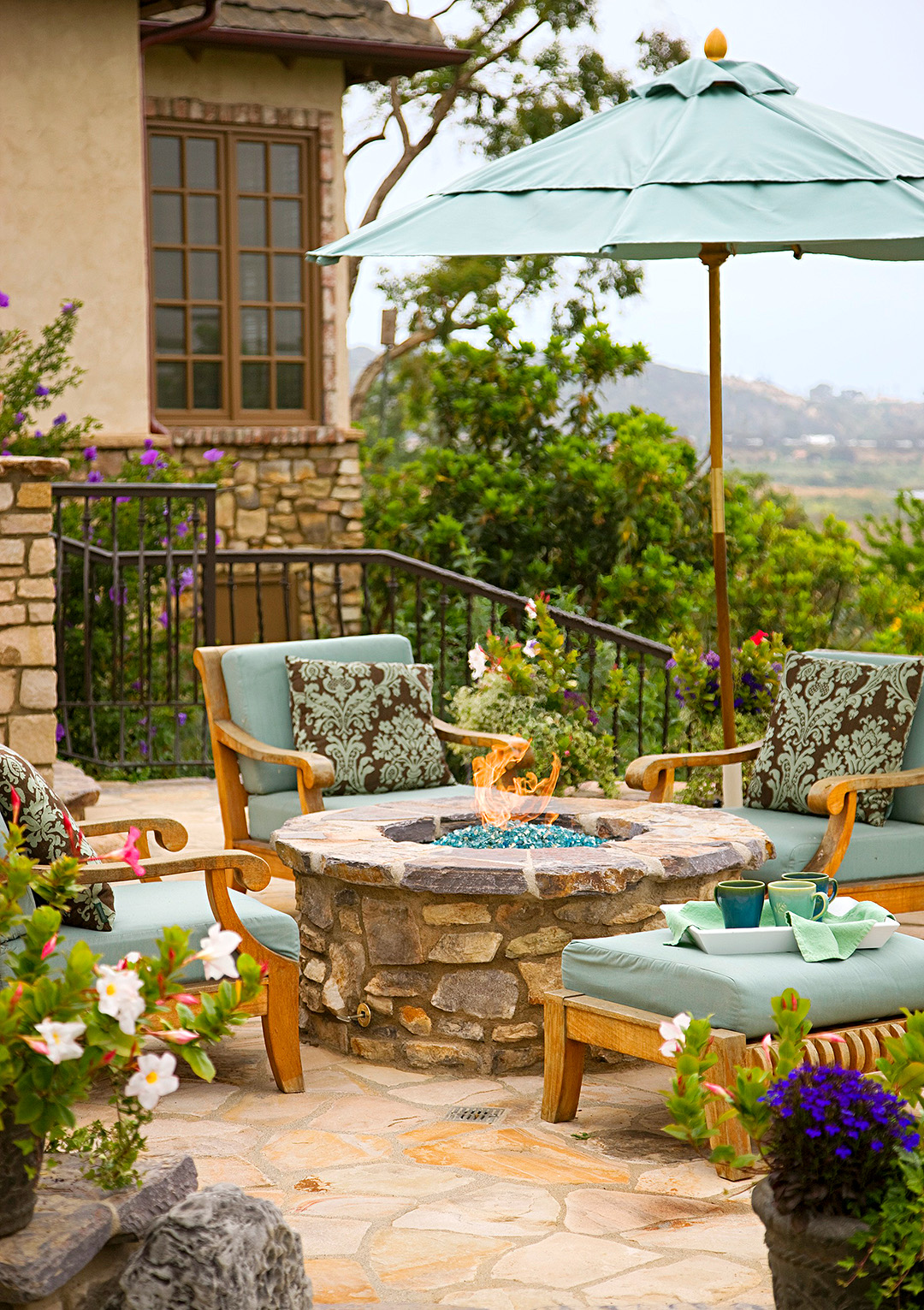 patio fire pit with outdoor chairs and teal cushions