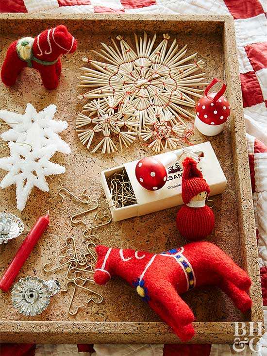arrangement of traditional Scandinavian ornaments, including salt snowflakes, straw ornaments, and Dala horses, on cork tray