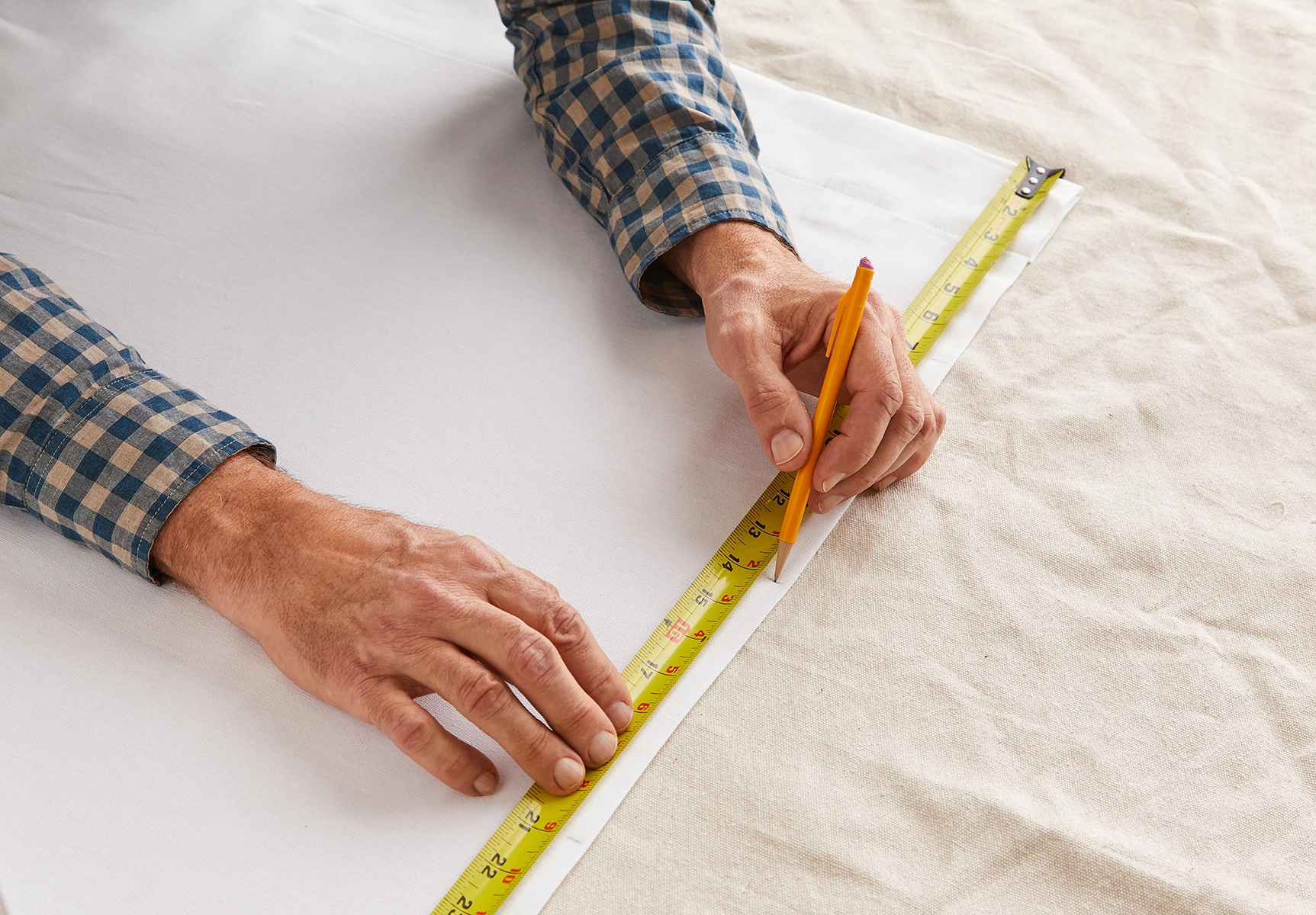 measuring curtain with measuring tape and pencil to add stripes