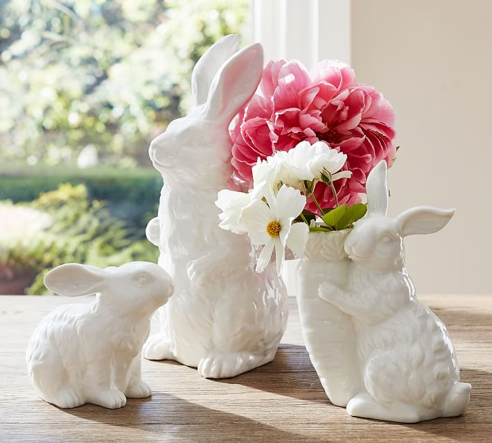 Three white ceramic bunnies on a front porch