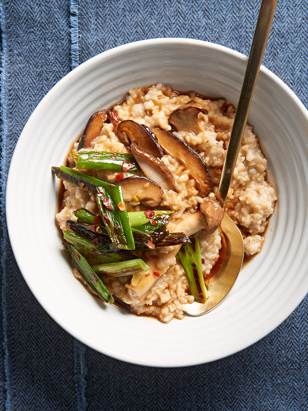 Ginger-Sesame Oats with Mushrooms and Charred Green Onions in white bowl with spoon