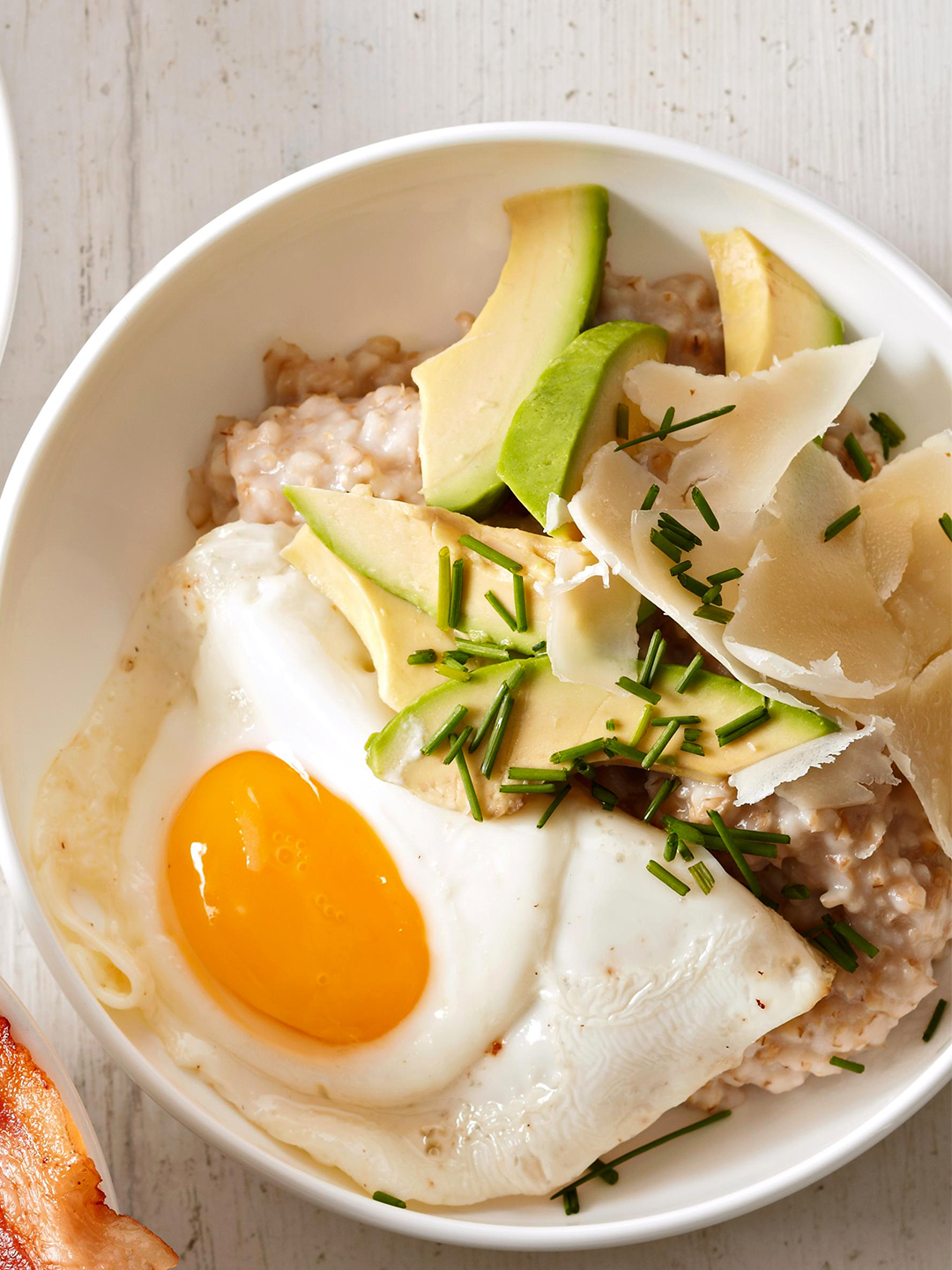 Oatmeal with Sunny-Side Up Eggs, Avocado, Cheddar, and Chives in white bowl