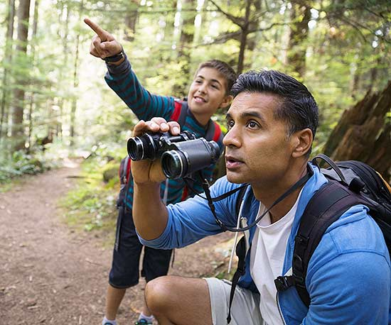 father and son walking along nature trail looking through binoculars