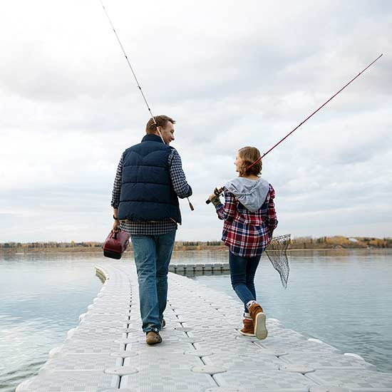 father and daughter holding fishing poles walking down dock