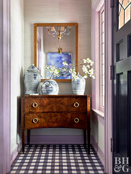 entry with table, mirror, and flowers