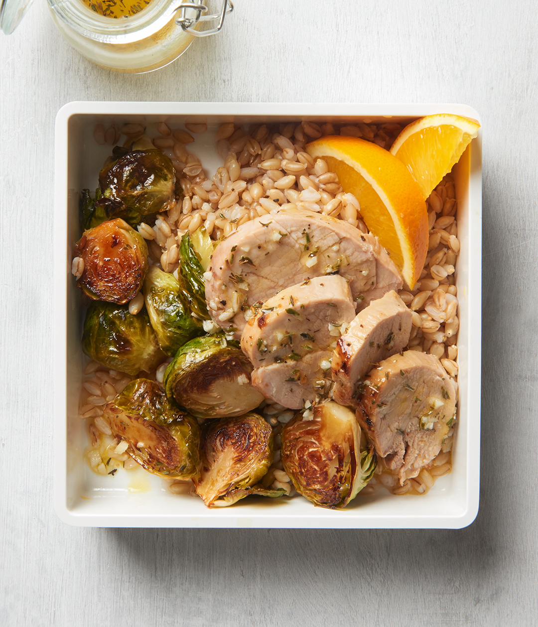 Pork, Brussels Sprouts, and Barley Bowls with orange slices