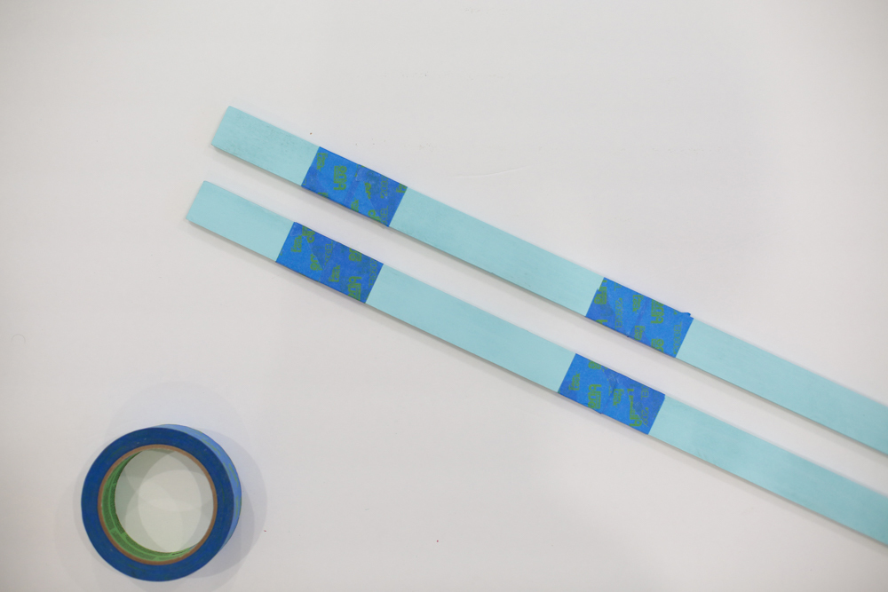 Blue wood stakes with painter's tape
