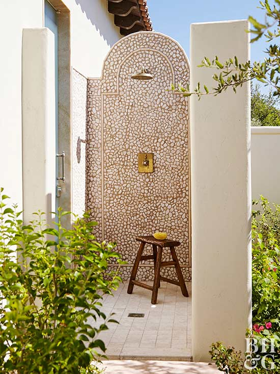 stone pebble tile outdoor shower with wooden bench
