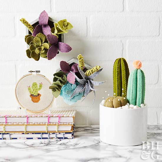 Artificial cactus with embroidery hoop and books on table against wall