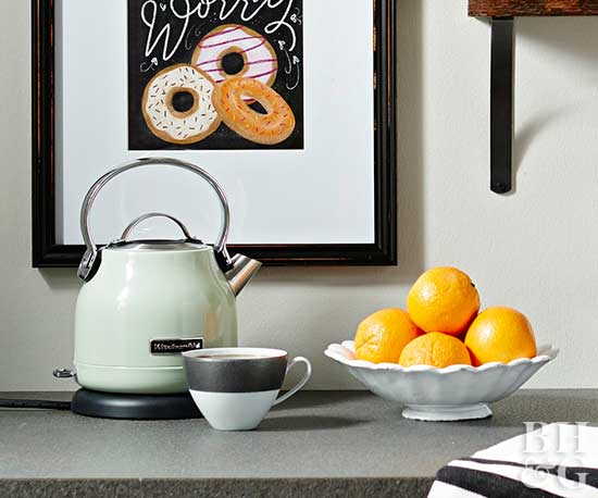 tea kettle and bowl of oranges on counter