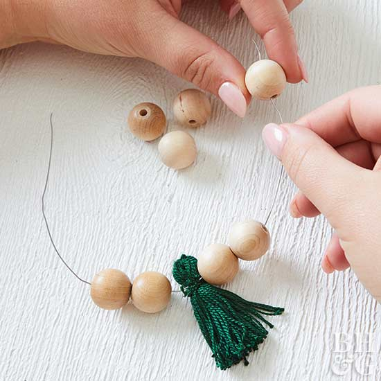 stringing beads to wood-bead-tassel ornament