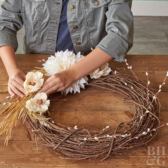 Applying white flowers to wreath