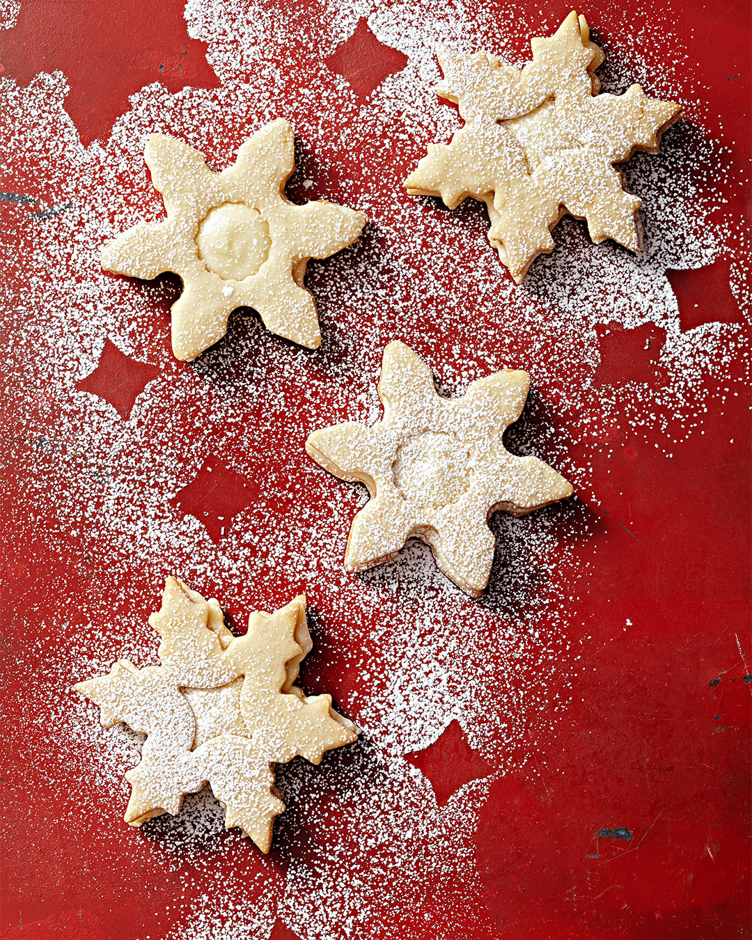 Lemony Snowflake Sandwich cookies on red table with powdered sugar