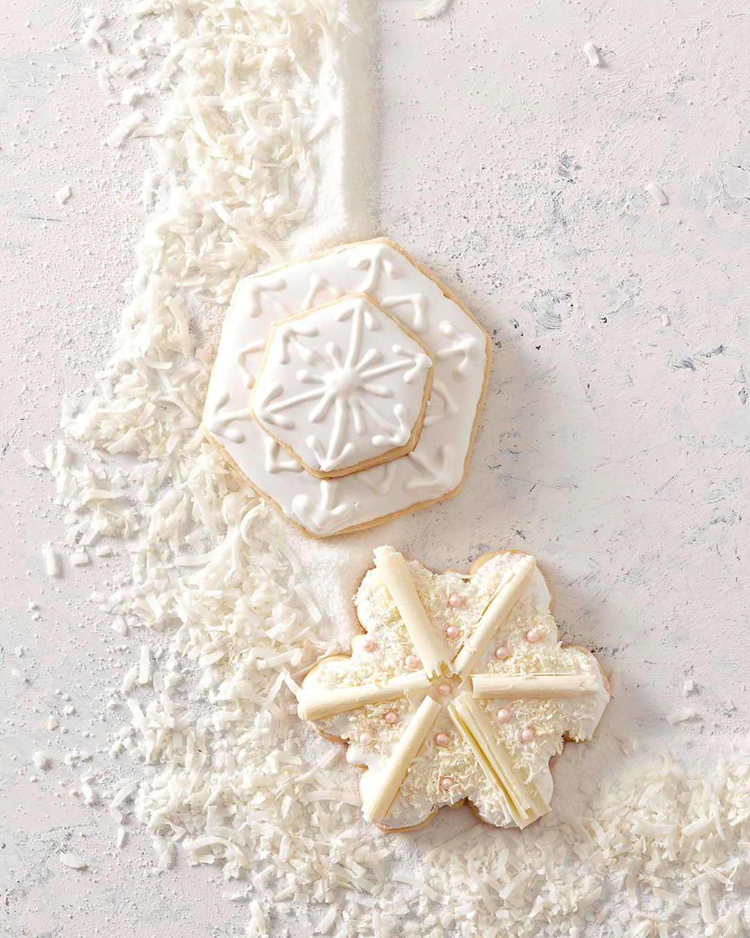 Almond Sugar Cookie Snowflakes on white surface with coconut shreds