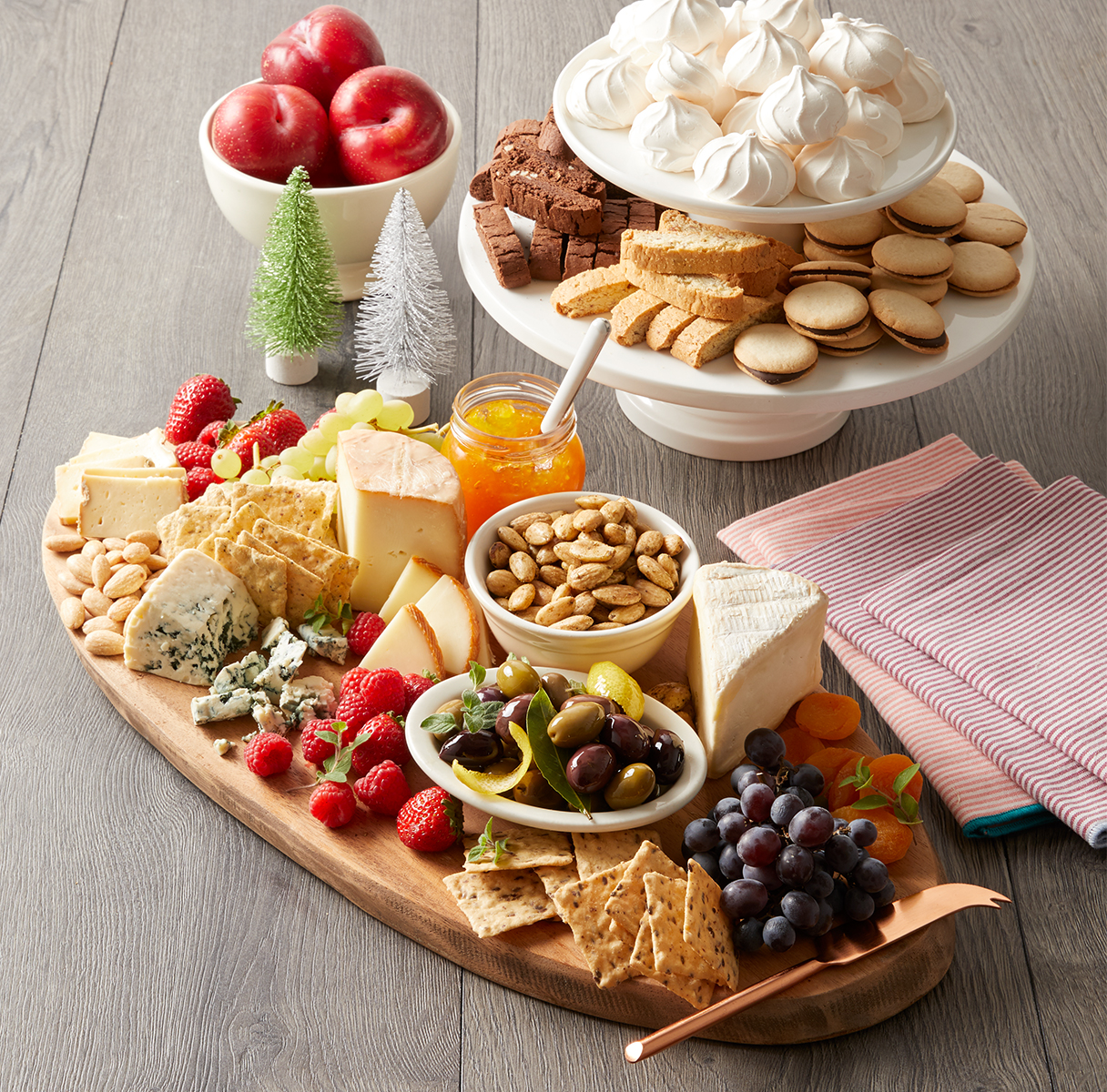 wooden board full of snacks with two-tiered dessert platter