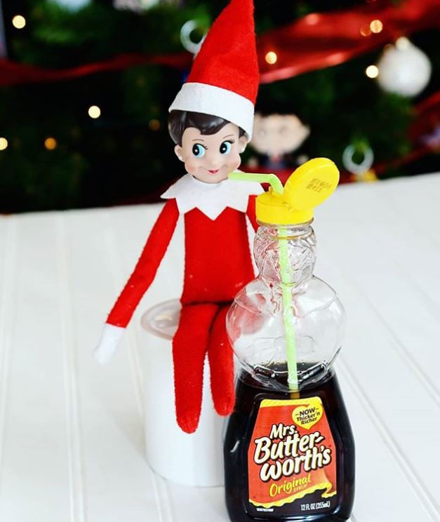 elf on the shelf doll pretending to drink syrup from the jar