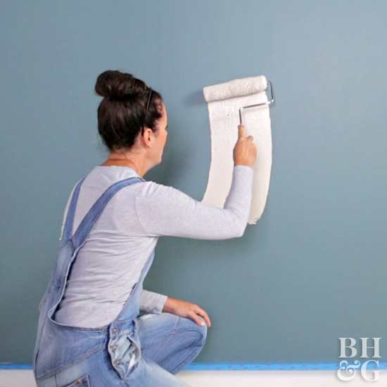 rolling neutral paint on teal wall