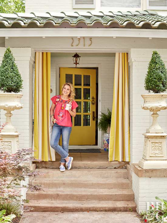 woman on front steps of white brick home