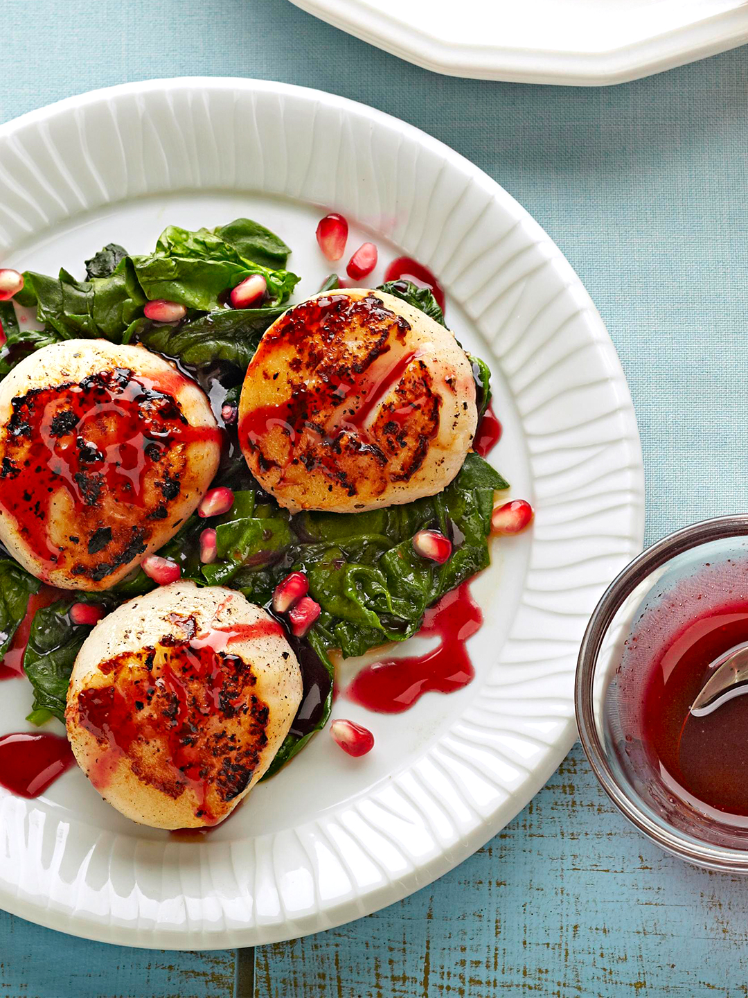 Seared Scallops and Baby Spinach with Spiced Pomegranate Glaze on white plate