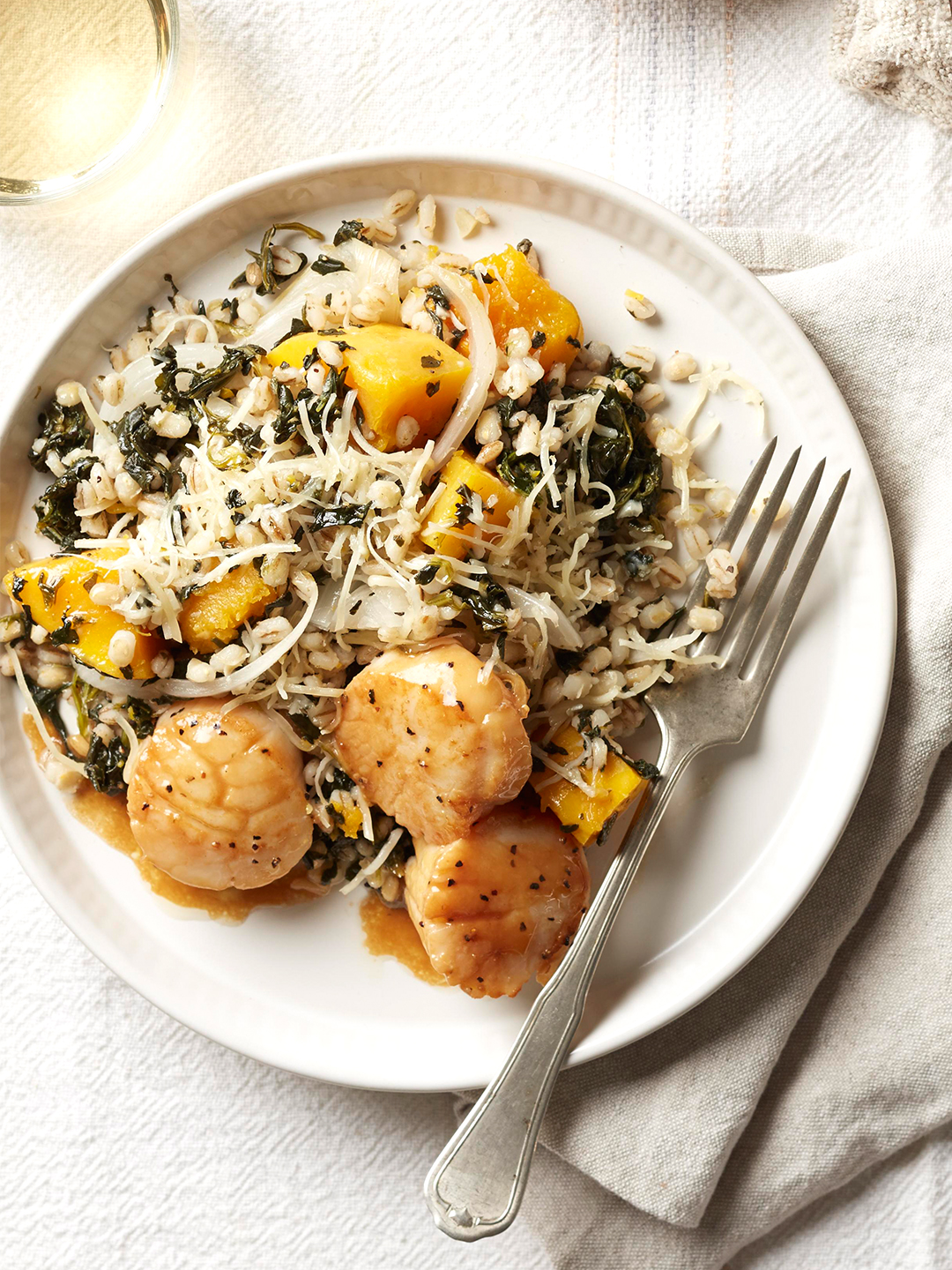 Barley-Squash Gratin with Scallops on white plate with fork