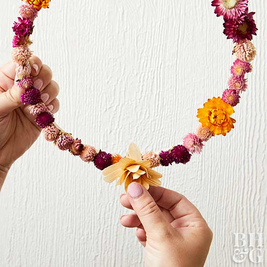 placing dried flower on wreath