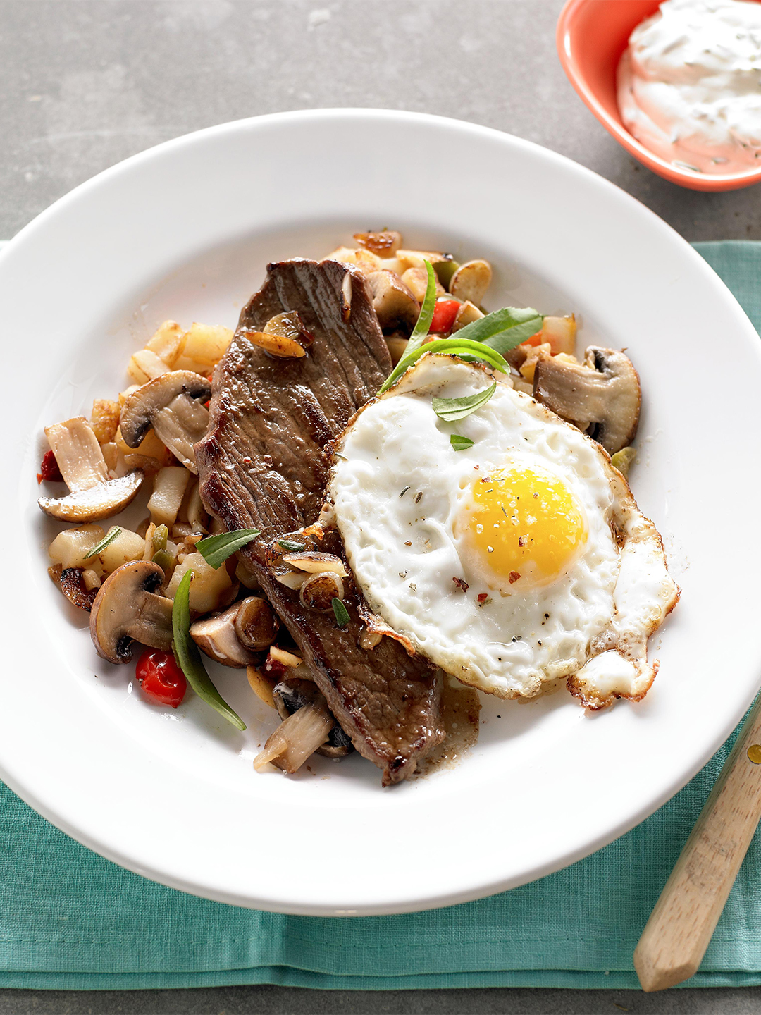Frizzled Eggs over Garlic Steak and Mushroom Hash in white bowl