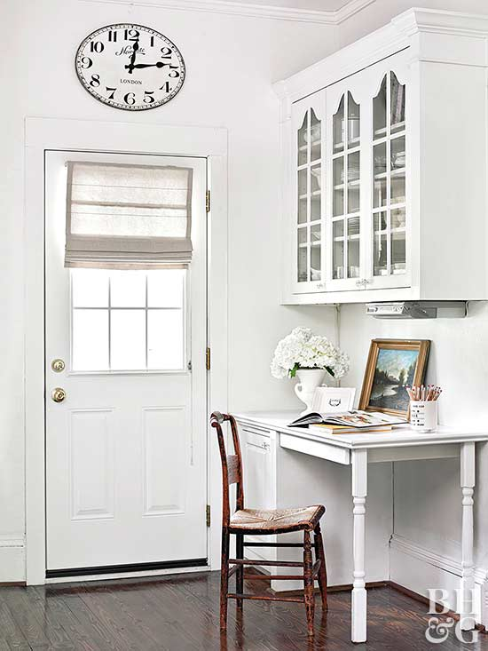 built in kitchen desk by entry way, glass door storage cabinets above desk