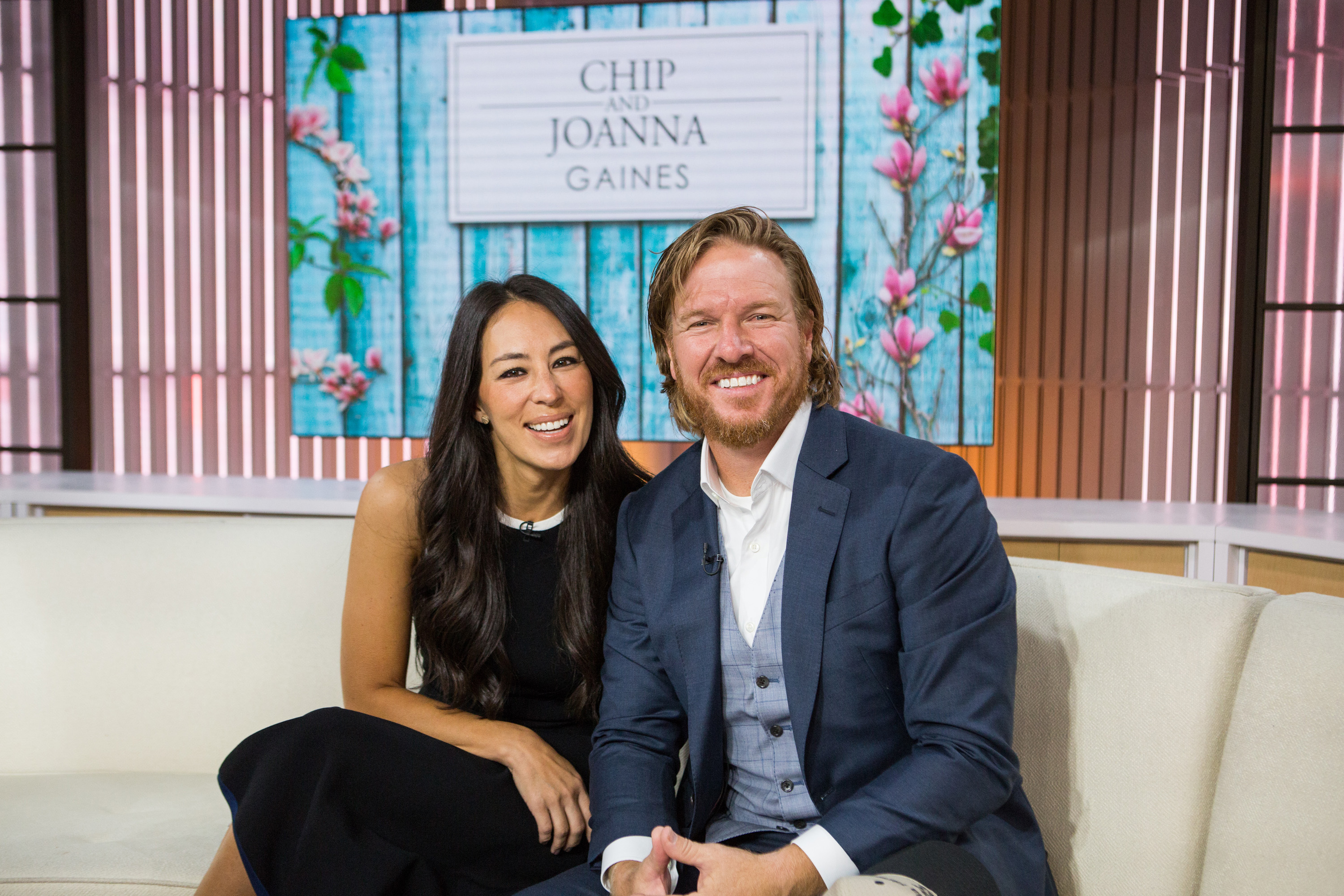 Chip and Joanna Gaines sitting on white couch