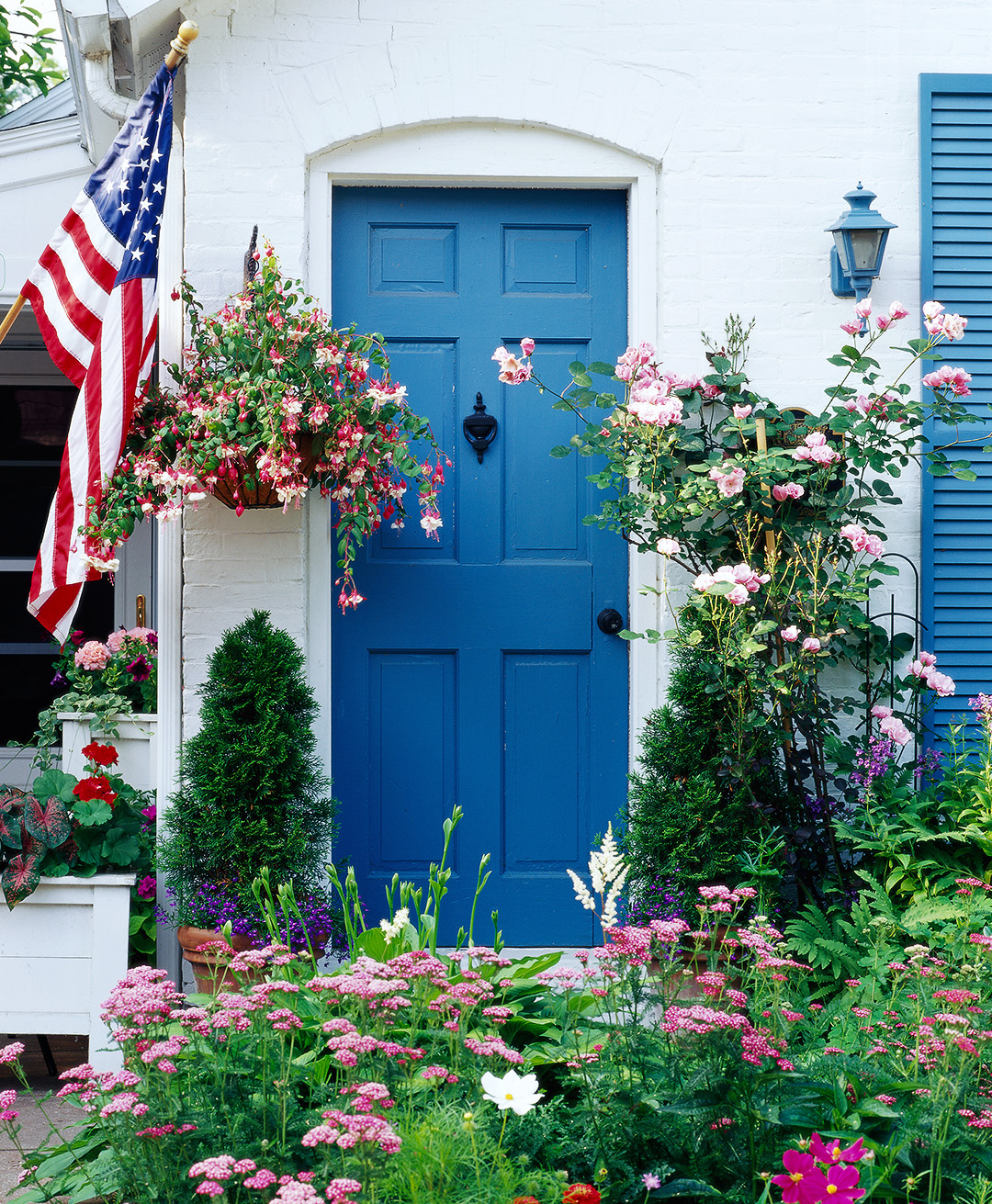 door yard garden blue door flag green flowers close up