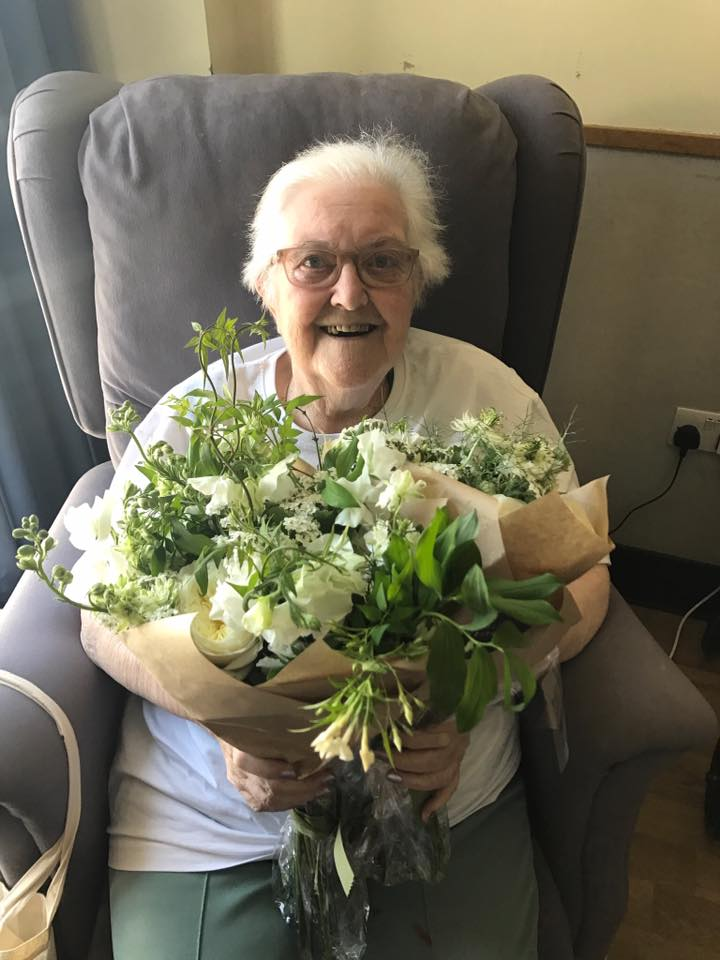 elderly woman holding flowers from the royal wedding at st joseph's hospice