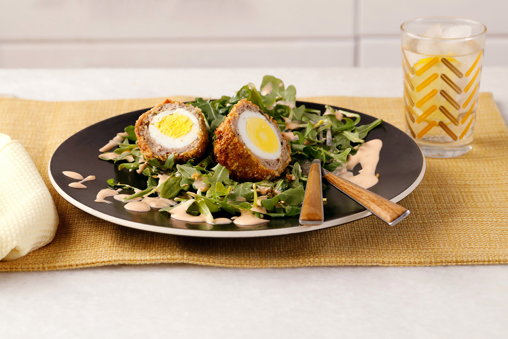 air fried scotch eggs on bed of arugula
