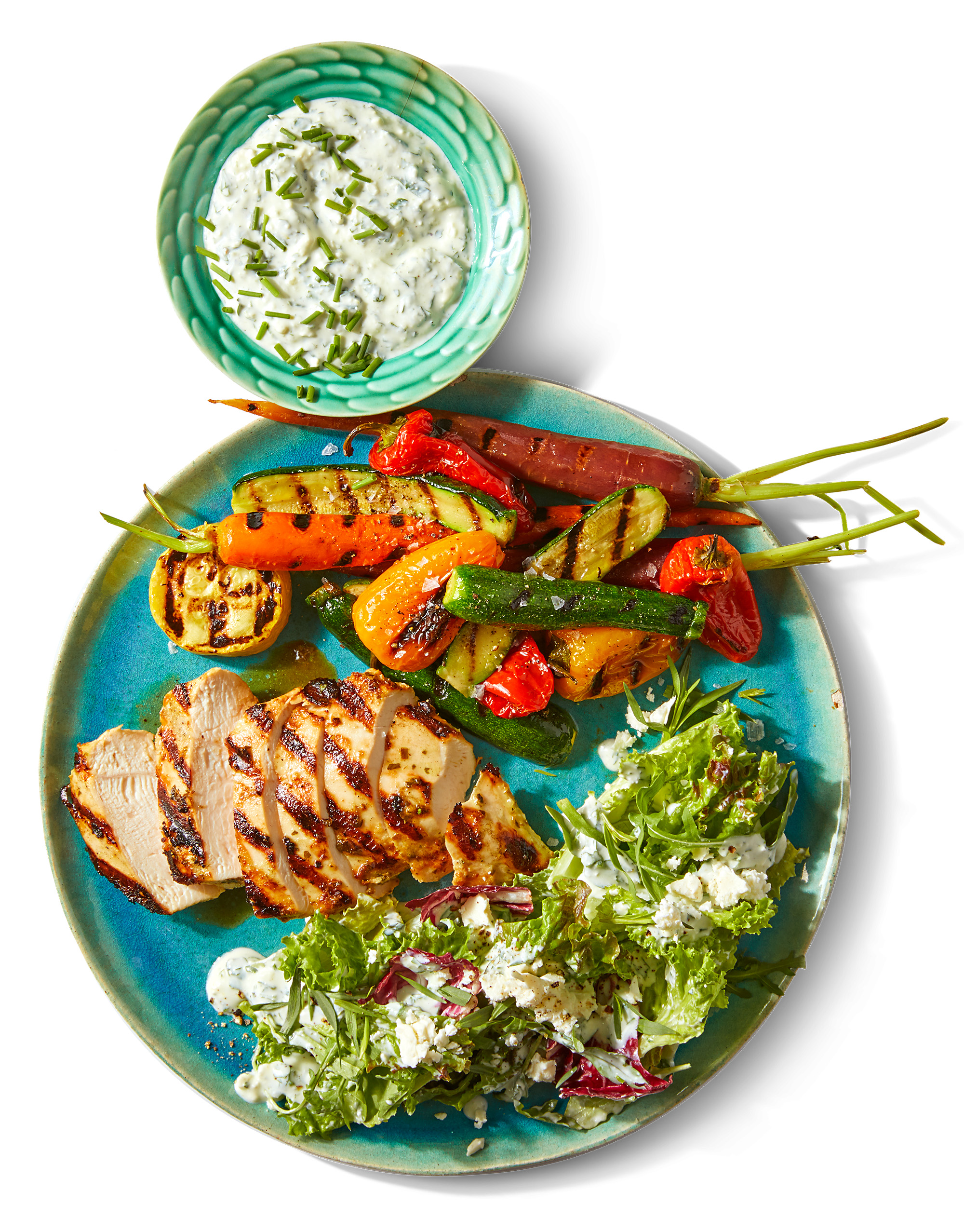 bowl of yogurt-feta dip plate of meat veggies