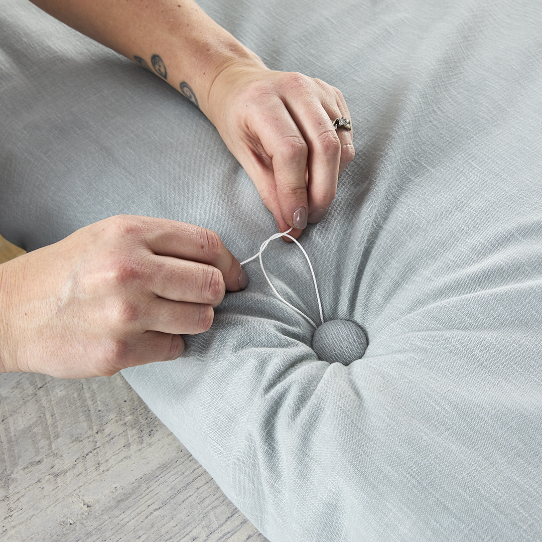 stitching button into tufted fabric bench