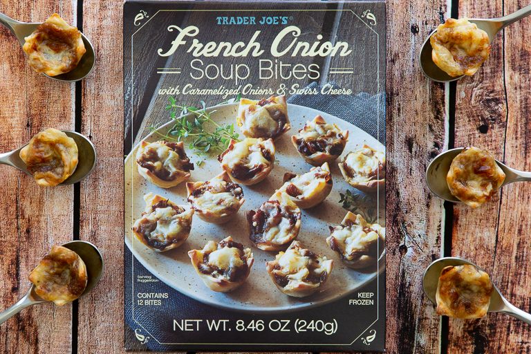 Box of Trader Joe's French Onion Soup Bites on wooden table surrounded by spoons