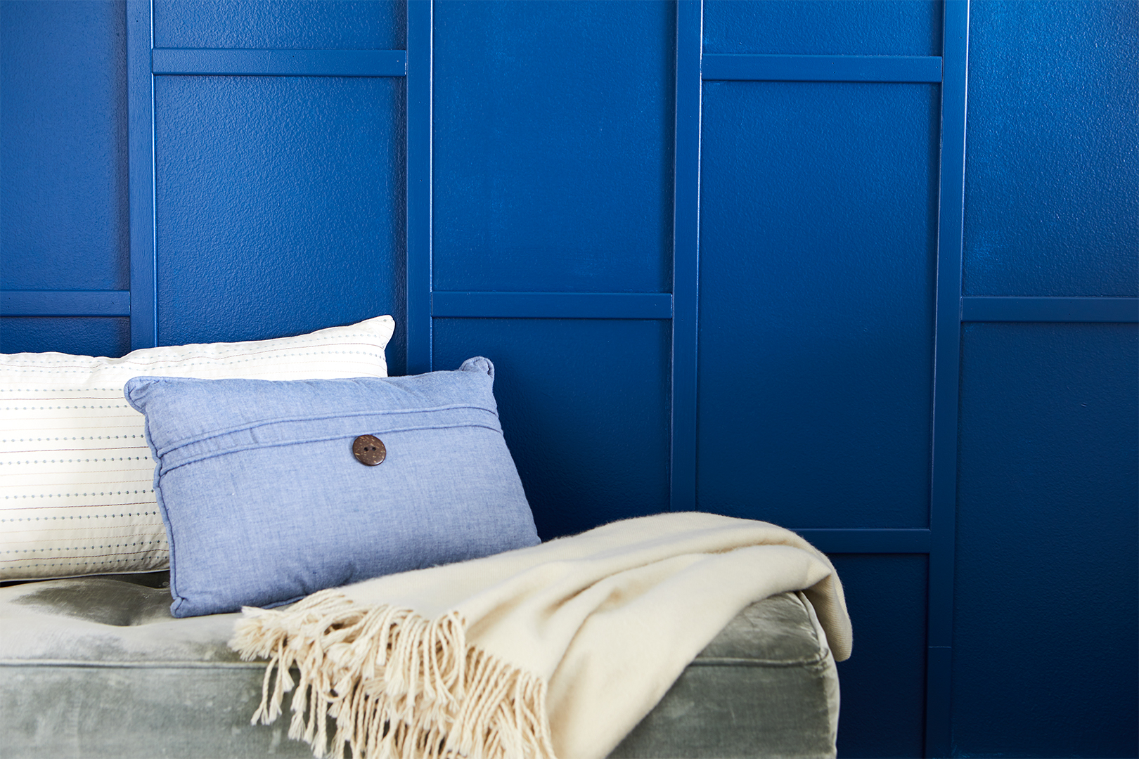 blue wall close-up ottoman throw pillows