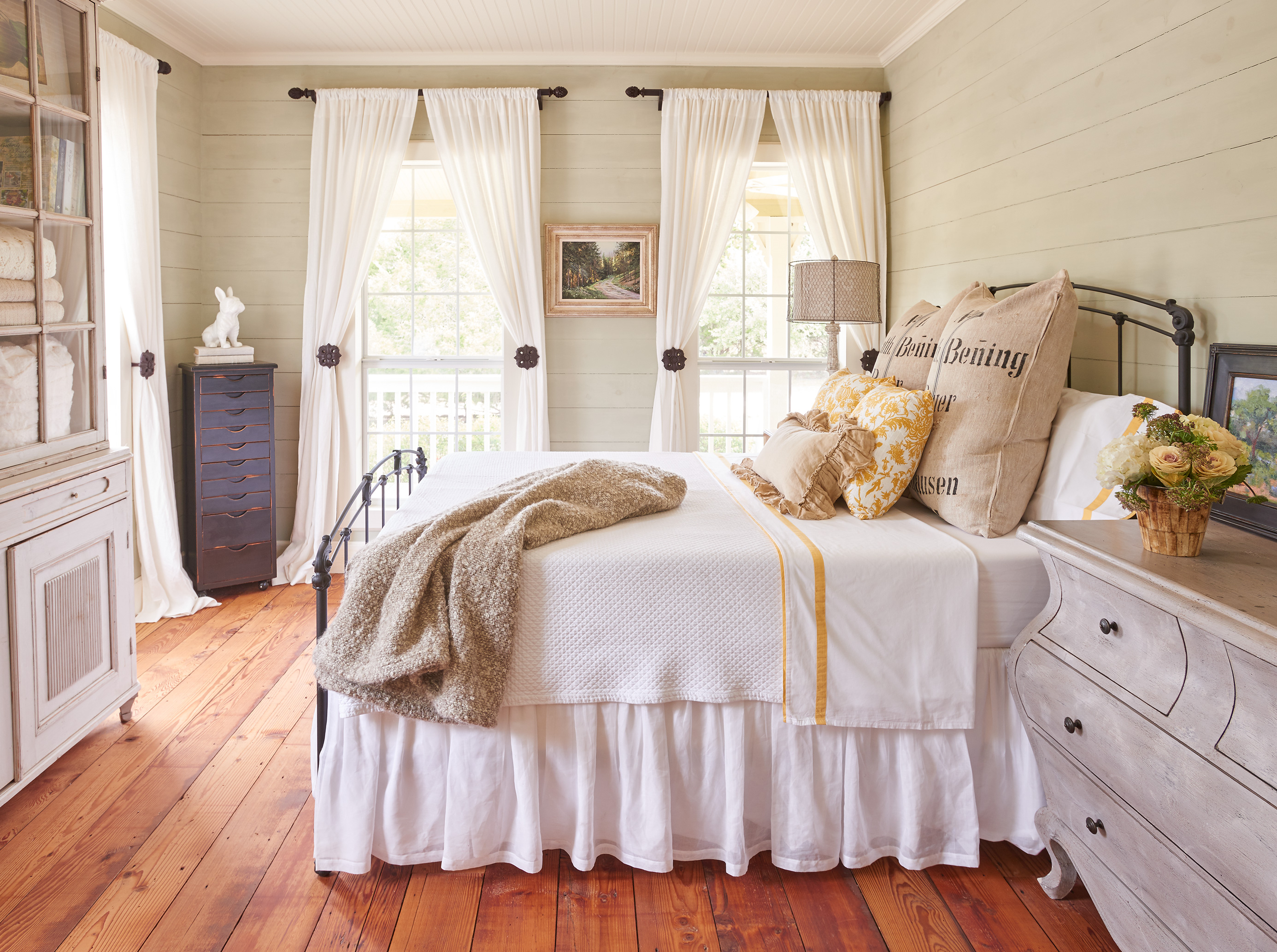 Country style bedroom with burlap pillows white curtains