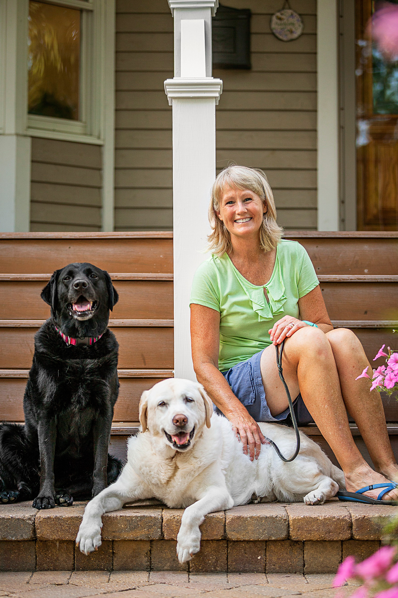woman with two therapy dogs on front steps
