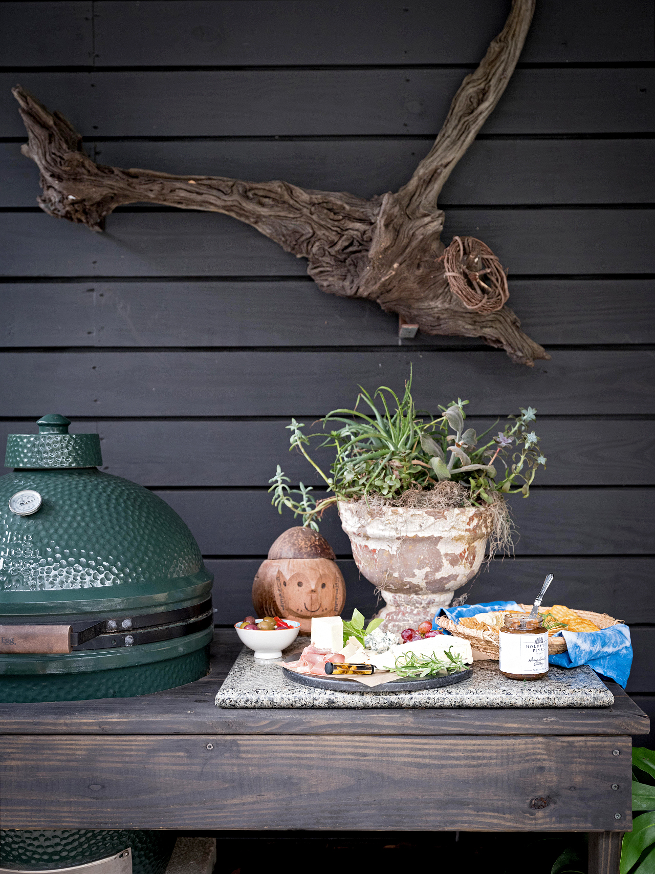 big green egg grill next to charcuterie on table