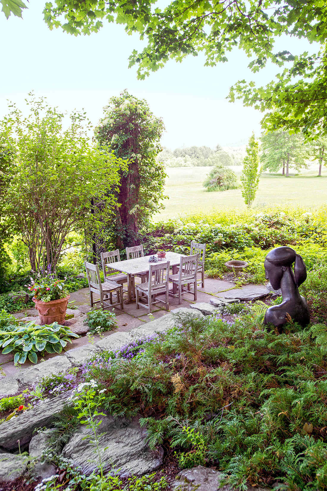 table and chairs surrounded by trees in garden