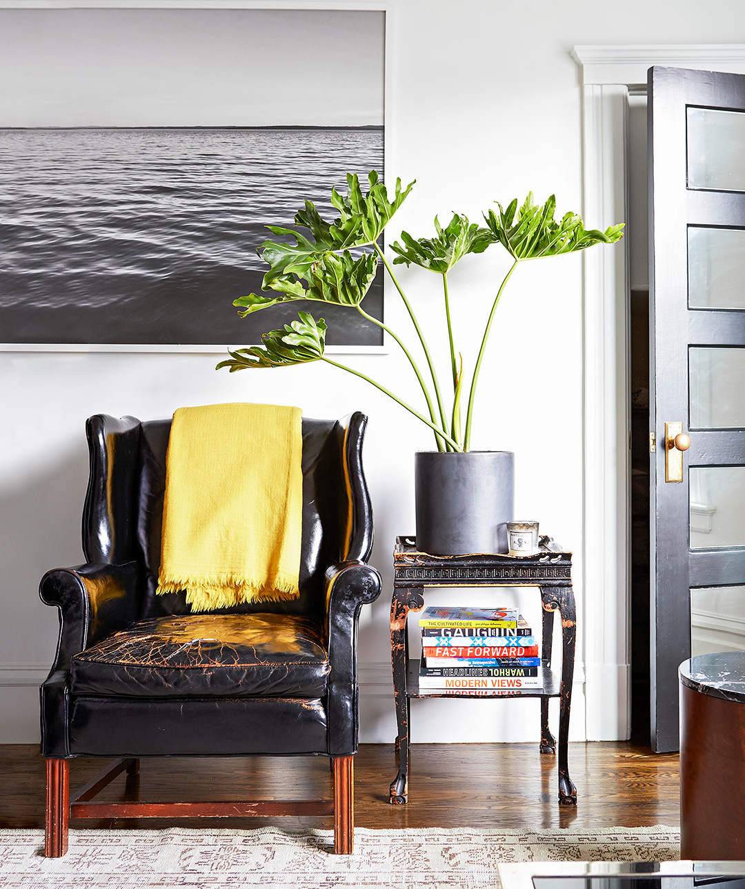 black leather chair with large photograph of the ocean above