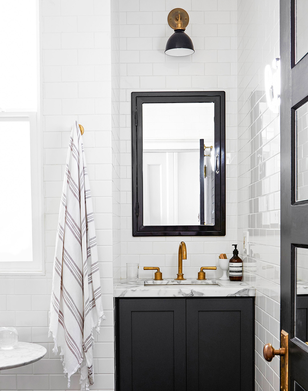 small modern bathroom with white subway tiles and black vanity